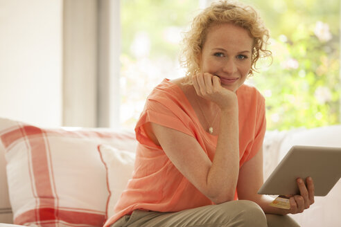 Portrait of woman using digital tablet on sofa - CAIF04556