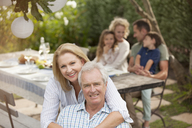 Portrait of smiling senior couple at family picnic - CAIF04562