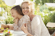 Mother and daughter smiling at table outdoors - CAIF04568