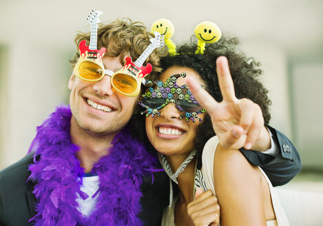 Couple wearing decorative glasses at party - CAIF04595