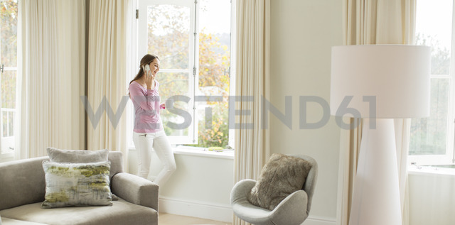 Woman drinking coffee and talking on cell phone at living room window - HOXF00215 - Tom Merton/Westend61