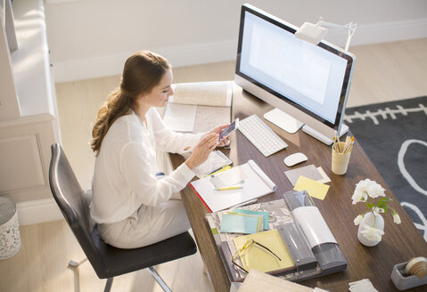 Interior designer texting on cell phone at desk in home office - HOXF00218