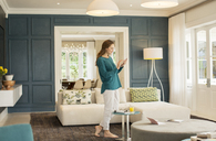 Woman texting with cell phone in home showcase living room - HOXF00221