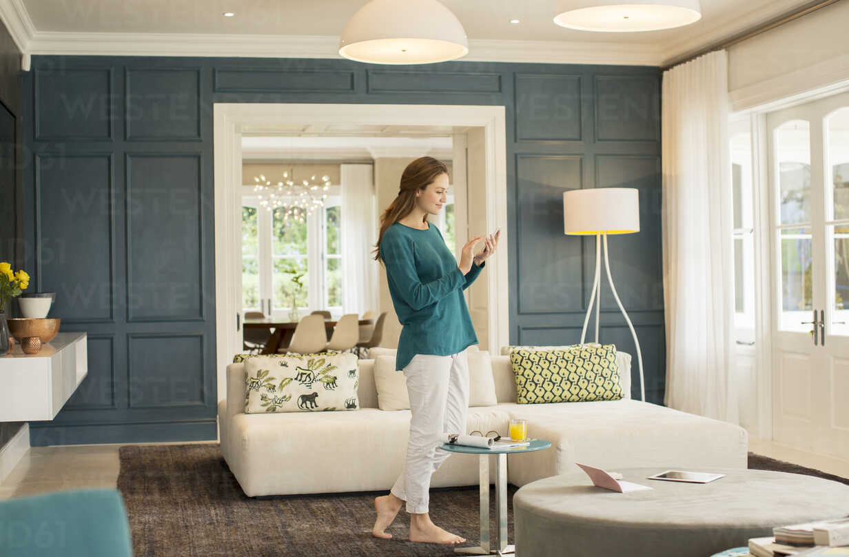 Woman texting with cell phone in home showcase living room - HOXF00221 - Tom Merton/Westend61