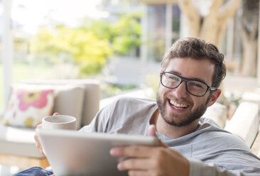 Portrait smiling man drink coffee and using digital tablet - HOXF00230