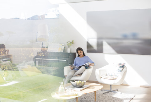 Woman reading magazine in sunny living room - HOXF00233