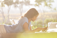 Woman laying using digital tablet on sunny patio - HOXF00245