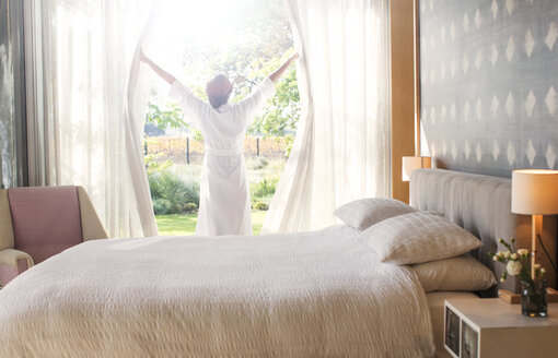 Woman in bathrobe opening bedroom curtains - HOXF00275