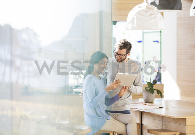 Couple using digital tablet in kitchen - HOXF00290