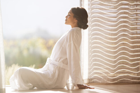 Serene woman in bathrobe sitting cross-legged at sunny doorway - HOXF00293