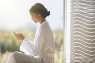Woman in bathrobe texting with cell phone in sunny doorway - HOXF00302