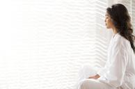 Serene woman in bathrobe meditating at sunny window - HOXF00311