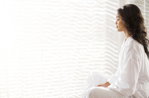 Serene woman in bathrobe meditating at sunny window - HOXF00311