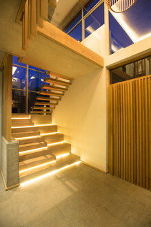 Illuminated modern stairs off foyer in luxury house - HOXF00317