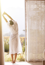Woman in bathrobe stretching with arms overhead at sunny patio doorway - HOXF00326
