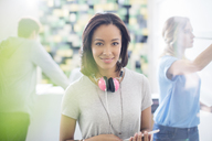 Portrait confident creative businesswoman with headphones in office - HOXF00350