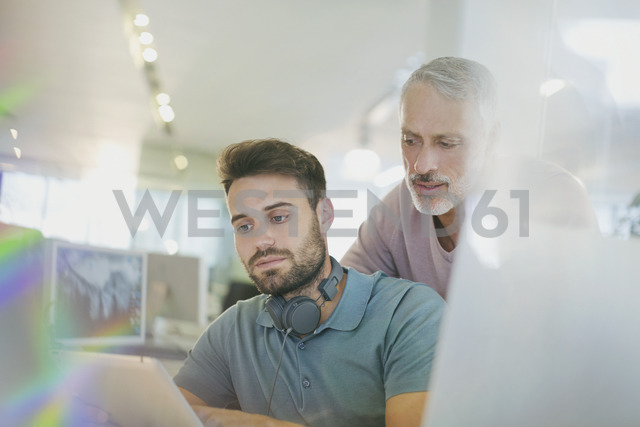 Creative businessmen using digital tablet in office - HOXF00365