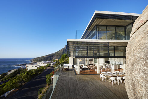 Modern luxury house and patio with ocean view under sunny blue sky - HOXF00458