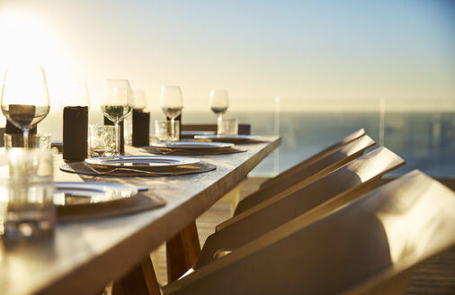 Sunset behind placesettings on luxury patio dining table - HOXF00467