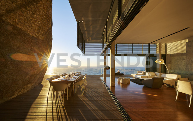 Sun setting behind modern luxury patio dining table with ocean view - HOXF00473