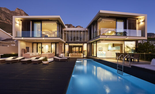 Modern luxury home showcase exterior and swimming pool illuminated at night - HOXF00491