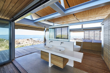 Modern luxury home showcase bathroom open to patio with ocean view - HOXF00500