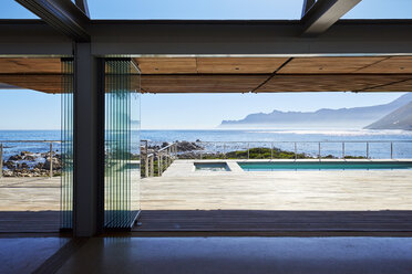 Modern luxury home showcase patio overlooking swimming pool and sunny ocean view - HOXF00503
