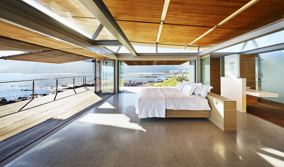 Modern luxury home showcase bed open to patio with sunny ocean view - HOXF00506