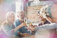 Friends toasting white wine glasses at restaurant table - HOXF00515