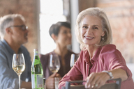 Portrait smiling senior woman dining with friends in restaurant - HOXF00554