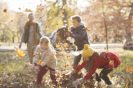 Family playing in autumn leaves at park - HOXF00572