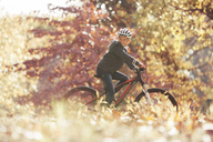 Boy bike riding in woods with autumn leaves - HOXF00578