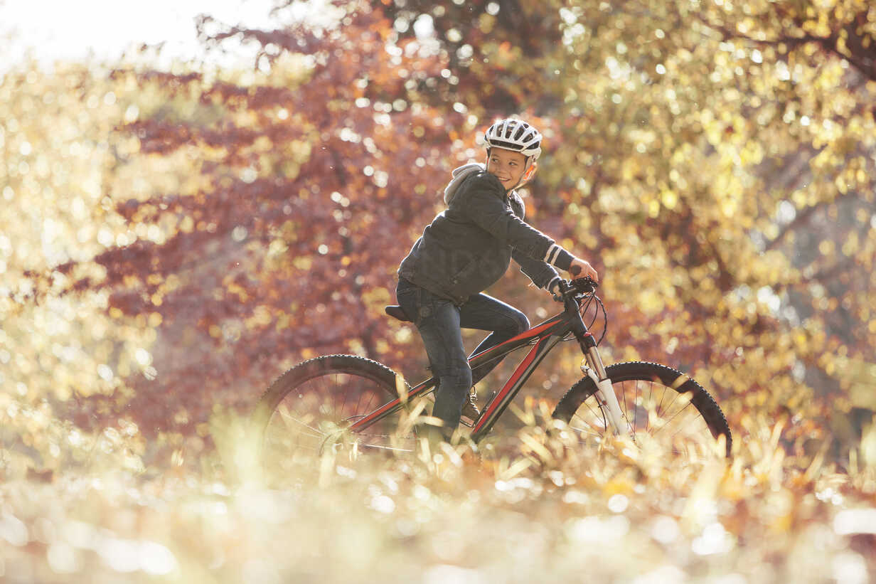 Boy bike riding in woods with autumn leaves - HOXF00578 - Tom Merton/Westend61