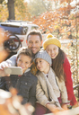 Family taking selfie among autumn leaves - HOXF00584