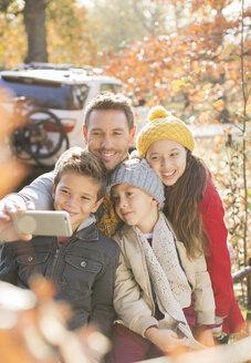 Family taking selfie among autumn leaves - HOXF00584