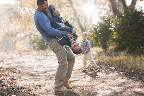 Playful father lifting son upside-down on path in woods - HOXF00590