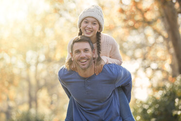Portrait enthusiastic father piggybacking daughter outdoors - HOXF00593