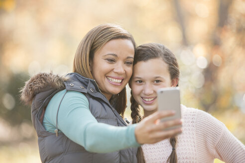 Mother and daughter taking selfie with camera phone outdoors - HOXF00596