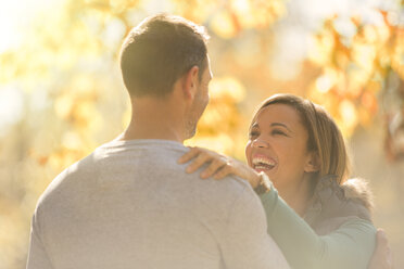Laughing couple face to face outdoors - HOXF00599