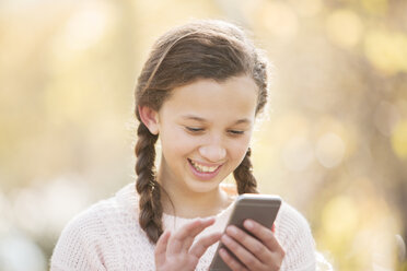Close up smiling girl texting with cell phone outdoors - HOXF00611