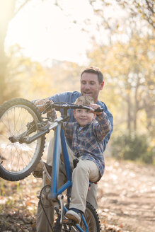 Father teaching son how to do a wheelie in woods - HOXF00614