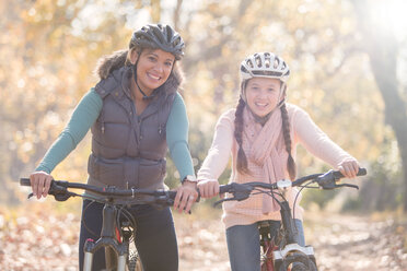 Portrait of smiling mother and daughter on mountain bikes in woods - HOXF00617
