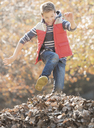 Enthusiastic boy jumping over pile of autumn leaves - HOXF00626