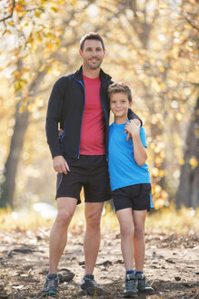Portrait smiling father and son in sportswear on path in woods - HOXF00629