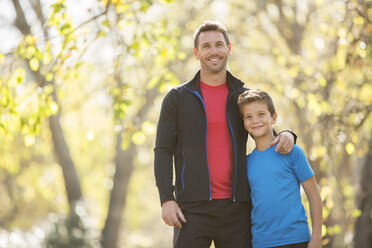 Portrait smiling father and son hugging outdoors - HOXF00632