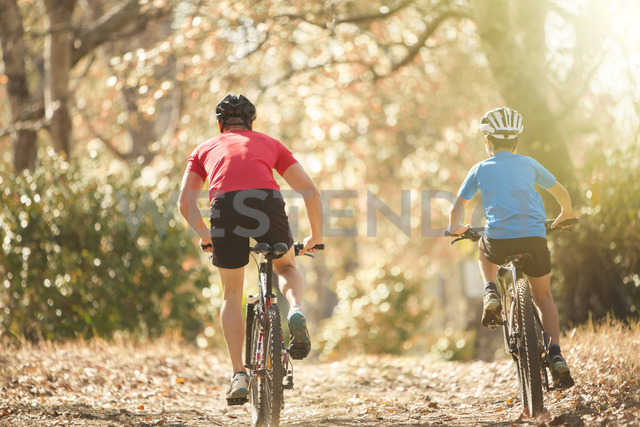 Father and son mountain biking on path in woods - HOXF00638