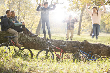 Family playing on fallen log with bicycles in woods - HOXF00641