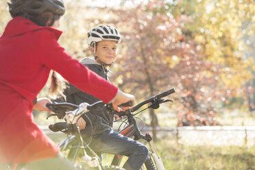 Portrait boy bike riding in autumn park - HOXF00644