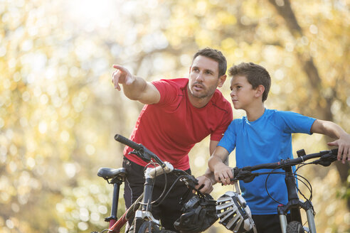 Father pointing and explaining to son on mountain bikes - HOXF00650
