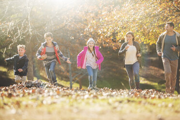 Family running in park with autumn leaves - HOXF00659